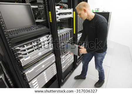 IT engineer installs blade server in datacenter