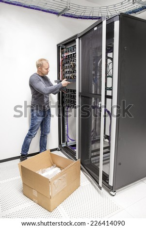 IT engineer installs network switch in datacenter - stock photo