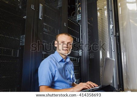 IT Engineer sitting on the floor between the rows in the Data Center and working on laptop