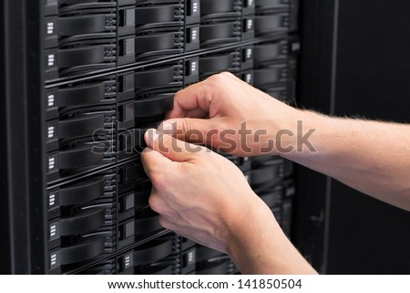 It engineer / technician working in a data center. Replace a hard drive in a SAN. - stock photo