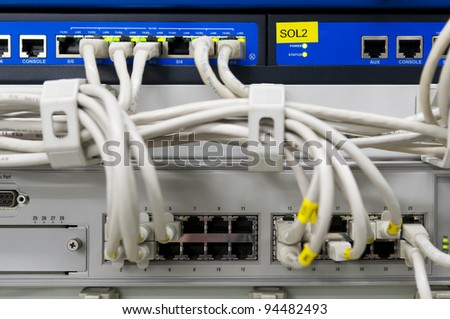 IT environment with switch and firewalls connected with grey patch ethernet cables
