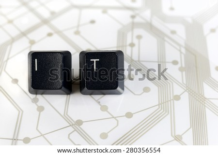 IT Helpdesk - Two Black Keyboard keys with letters I and T on White Circuit Board Background - stock photo