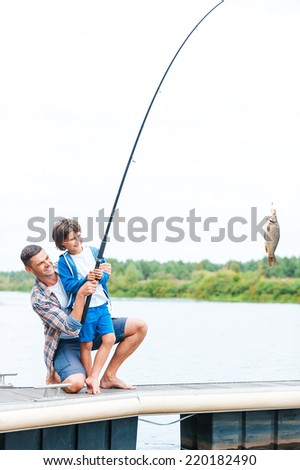 It is a big fish! Father and son stretching a fishing rod with fish on the hook  - stock photo
