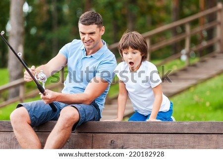 It is a big fish! Happy father and son fishing together while little boy looking excited and keeping mouth open - stock photo