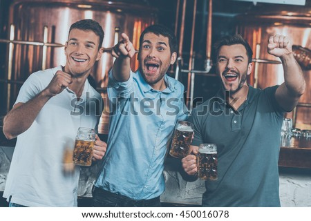 It is a goal! Three happy men holding beer mugs and gesturing while watching TV in bar - stock photo