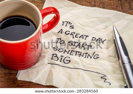 It is a great day to start something big - motivational handwriting on a napkin with a cup of coffee - stock photo