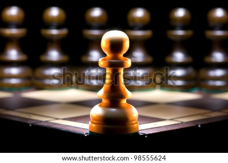 It is a lot of chessmen on a chess board. (are located it is horizontal). A black background. - stock photo