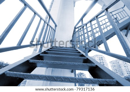 It is a modern gray stair outside of buildings.