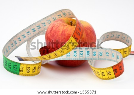 it is a red apple with the tape to measure. shallow DoF with focus on front of measuring tape. - stock photo