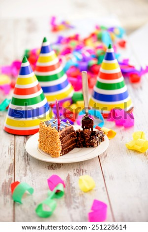 It is a special day. Image of a delicious chocolate cake with a candle and fork surrounded by party hats and confetti on the background