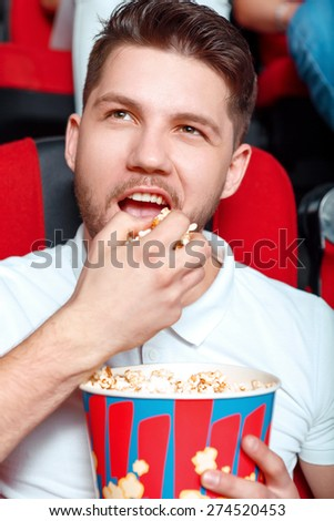 It is all mine. Young man greedy eating popcorn in cinema while watching film.