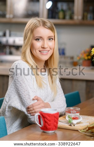 It is already lunch time. Pleasant cheerful attractive girl sitting at the table and eating dessert while having lunch in the cafe