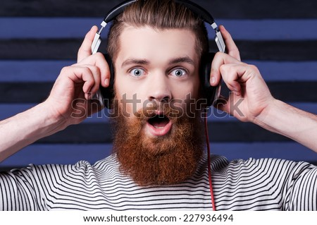 It is amazing song. Confident young bearded man in headphones standing against stripped background and listening to the music - stock photo