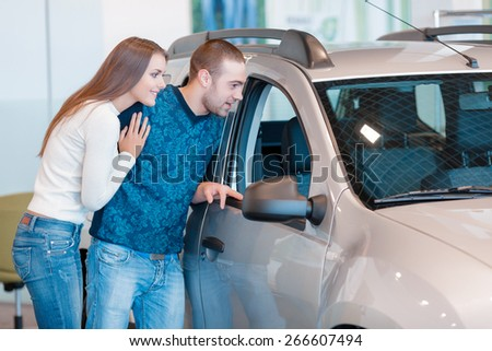 It is beautiful. Smiling young couple standing alongside a car and leaning against it watch at the interior of a new car