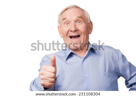 It is cool! Excited senior man stretching out his hand with thumb up while standing against white background  - stock photo