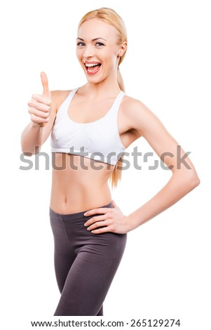 It is cool to be healthy and slim! Beautiful mature women showing her thumb up and smiling while standing against white background