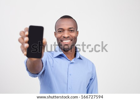 It is for you. Cheerful black man stretching out a mobile phone and smiling while standing isolated on grey - stock photo