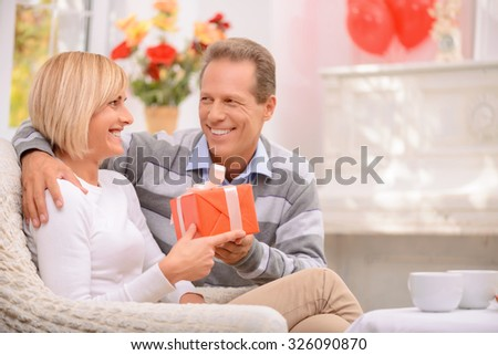 It is for you. Overjoyed happy adult couple holding present and sitting on the settee while celebrating St Valentine Day  - stock photo