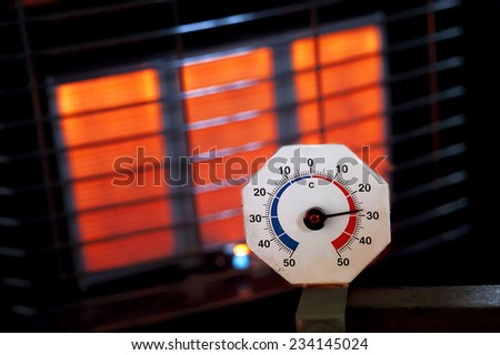 It is getting warmer, close up of an old analogue thermometer with a gas heater in the background - stock photo
