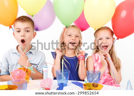 It is great birthday party. Cheerful children holding balloons and sitting at the table.  - stock photo
