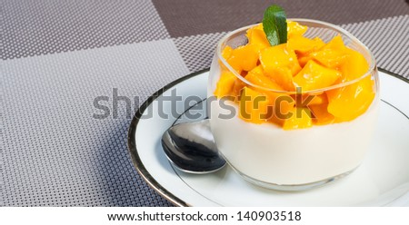 it is made of cream and gelatin and mix with flavourings and topped with fruits or any solid food/mango panna cotta - stock photo
