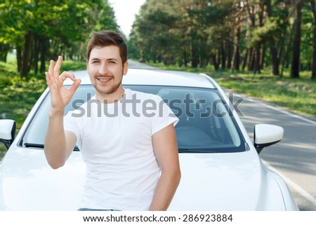 It is ok. Young attractive smiling man with beard standing in front of new car and showing ok. - stock photo