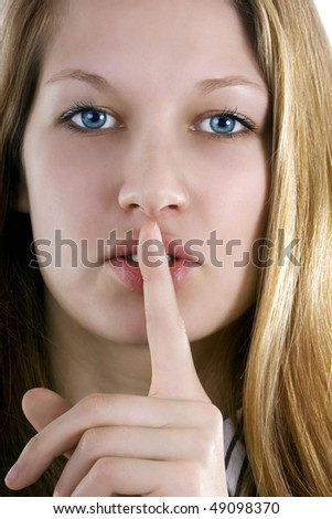 It is our secret - beautiful woman with forefinger before mouth - stock photo
