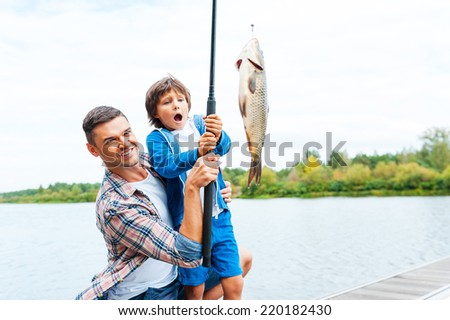 It is so big! Father and son stretching a fishing rod with fish on the hook while little boy looking excited and keeping mouth open - stock photo