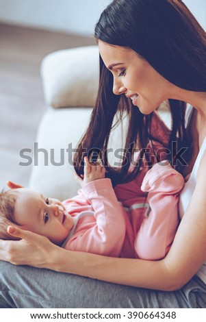 It is so nice to play with mommys hair! Side view of cheerful beautiful young woman holding playful baby girl on her knees and looking at her with love while sitting on the couch at home - stock photo