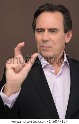 It is this small. Mature businessman gesturing small size by his fingers while standing on brown background