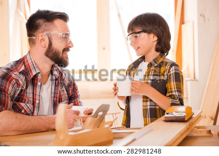 It is time for taking break. Smiling young male carpenter and his son holding cups and looking at each other while working in workshop - stock photo