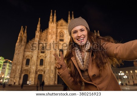 It is time to dress up and take a night tour in ultra-luxurious fashion expert - Milan, Italy. Smiling young woman showing victory gesture and taking selfie in the front of Duomo in the evening.