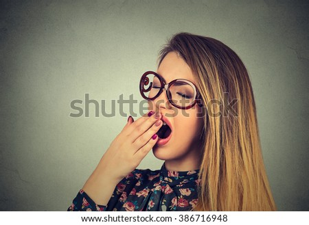 It is too early for meeting. Closeup portrait sleepy young woman with wide open mouth yawning eyes closed looking bored isolated on gray wall background. Face expression emotion body language - stock photo