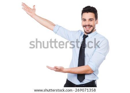 It is unbelievable! Happy young man in shirt and tie pointing away and smiling while standing against white background - stock photo