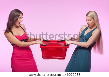 It�¯�¿�½ mine! Two angry young women trying to take away one shopping basket while isolated on pink background - stock photo