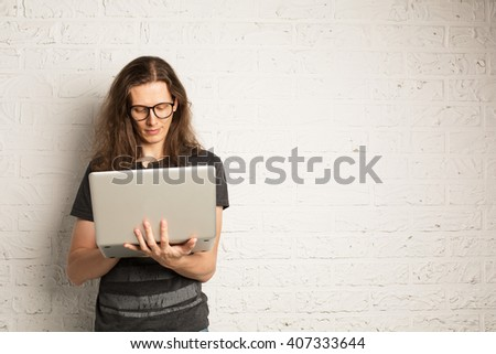 IT programmer man with glasses and long hair staying near white brick wall with laptop computer  - stock photo