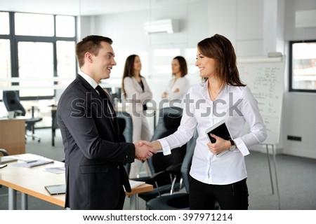 It's a deal! Business people handshaking. Their colleagues on a background. - stock photo