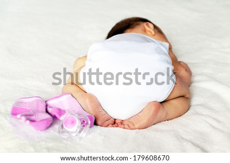 it's a girl! newborn baby. butt in a diaper, with a adorable crossed legs and feet - stock photo