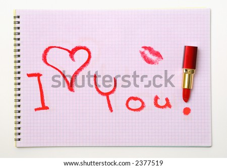 It's an 'I love you!' message written on a pink sheet of paper with the red lipstick. - stock photo