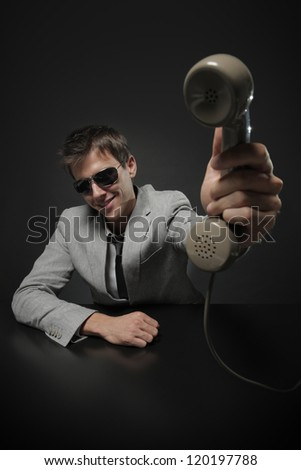 It's for you! Businessman holding retro telephone - stock photo