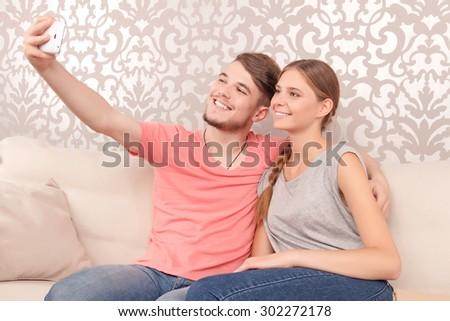 It s selfie time. Content smiling young husband holding mobile phone and sitting on the settee with his wife while bonding to each other. - stock photo