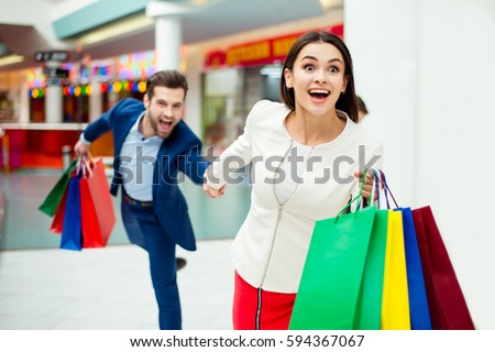 It's shopping and fun time. Portrait of cheerful successful happy young lovely couple holding colored shopping bags and laughing in mall. Concept of consumerism, sale, rich life.