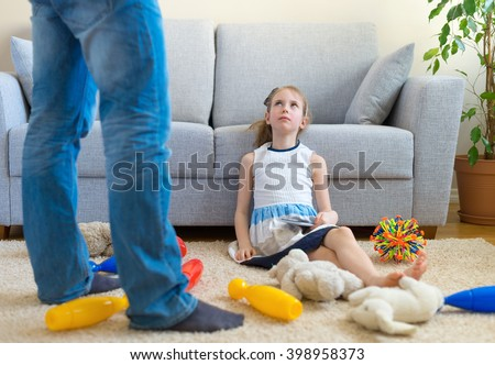 It's time to clean up your toys! Little girl playing with tablet pc, ignoring her father.