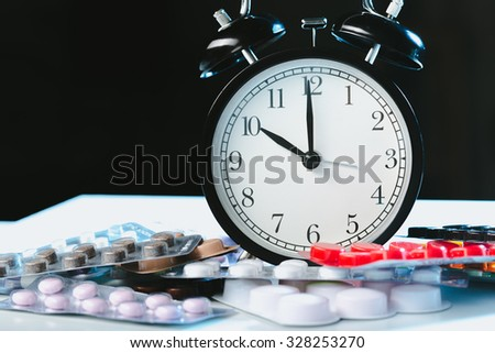 It's time to take pills! Medicine and clock - stock photo
