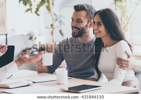 It seems to be a good proposition. Cheerful young couple bonding to each other and smiling while looking at some man sitting in front of them and gesturing - stock photo