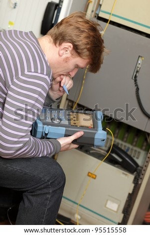 IT technician commissioning of fibre optic by analyser - stock photo
