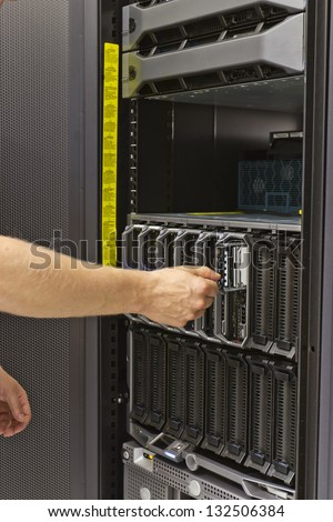 """IT technician / consultant insert / remove a hard disk from a blade server in a data center. This is a 2,5"""" hard drive. - stock photo"""