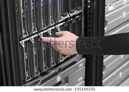 IT technician / engineer power on and install / removes / replace a blade server in a data center. - stock photo