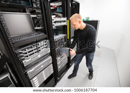 IT Technician Installing Blade Server In Chassis At Datacenter