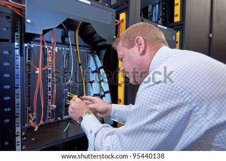 IT technician working on network servers and cables. - stock photo
